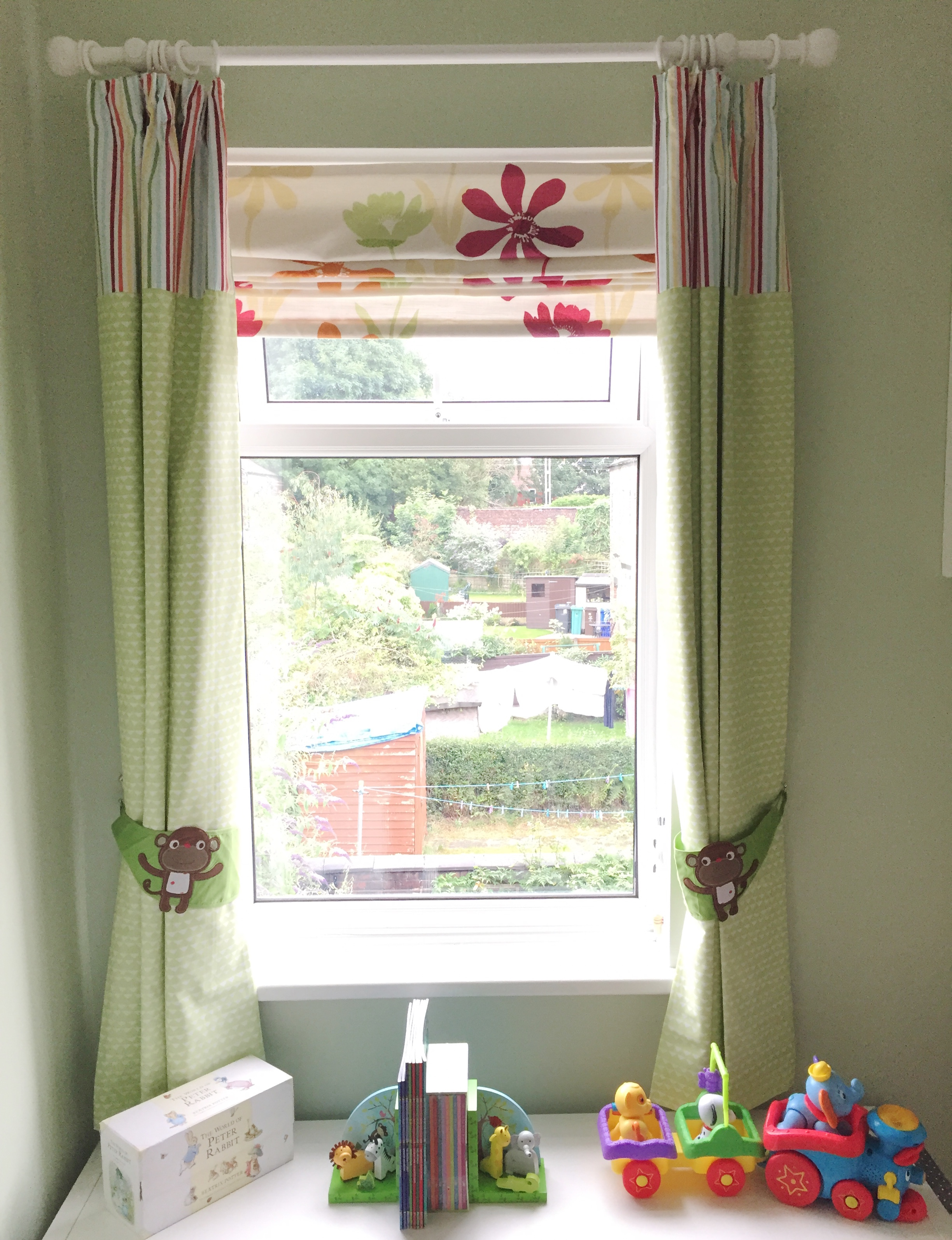 Nursery window with green curtains, monkey tie backs and storage unit underneath