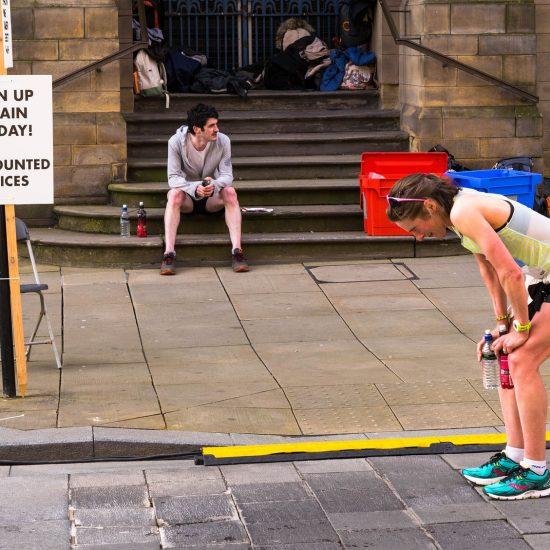 Marathon runner taking a breather with a sign saying 'Sign up again today! Discounted prices'